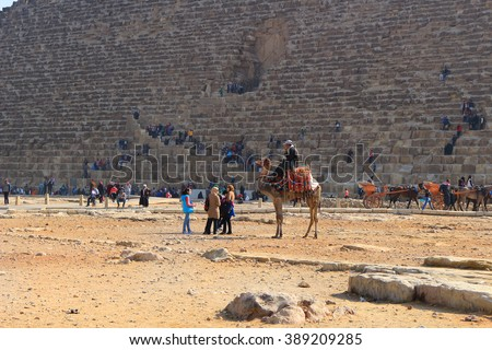 GIZA PLATEAU, EGYPT - JAN. 31, 2016: Tourists and visitors at the bottom of the Grand Pyramid walking, going on camel and horseback in the golden desert sands in Egypt - stock photo
