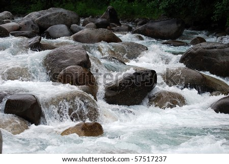 Glacial gold river rushing over boulders in Alaska - stock photo