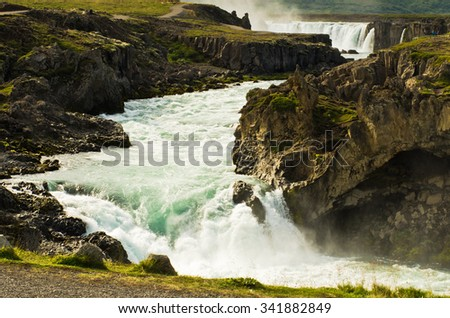 Glacial river with Godafoss waterfall in background, north Iceland - stock photo
