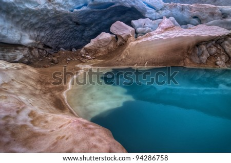 Glacier cave above brilliantly turquoise melt pool - stock photo