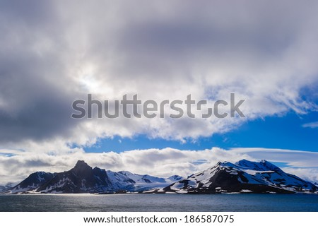 Glacier heading down from a mountain range into the Arctic Ocean, Hornsund, Norway
