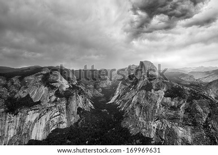 Glacier Point, an overlook with a commanding view of Half Dome, Yosemite Falls,  in a dramatic black and white composition with heavy clouds, Yosemite National Park, California, USA - stock photo
