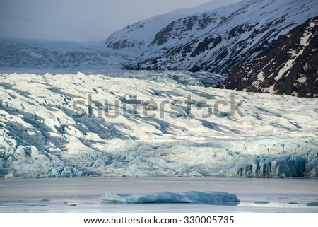 Glacier tongue between the mountains coming into glacial lake, Vatnajokull glacier, Fjallsarlon lagoon, South Iceland