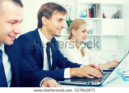 Glad business male assistant wearing formalwear using laptop and sitting with coworkers in company office