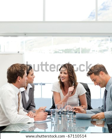 Glad businesswoman talking to her team during a meeting - stock photo