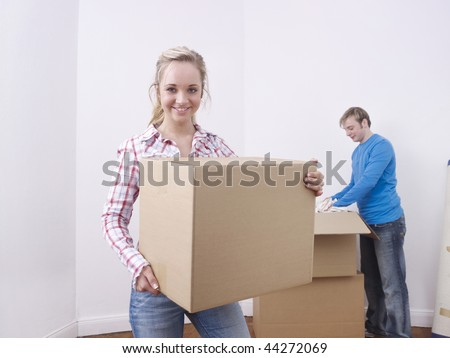Glad couple in white room unpacking cardboard boxes. - stock photo