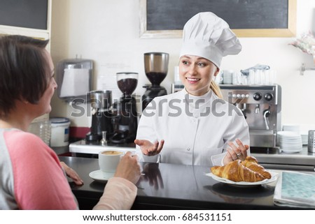 Glad friendly smiling female cook serving a dessert to the customer in the cafe counter