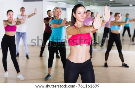 glad people of different ages posing in fitness studio