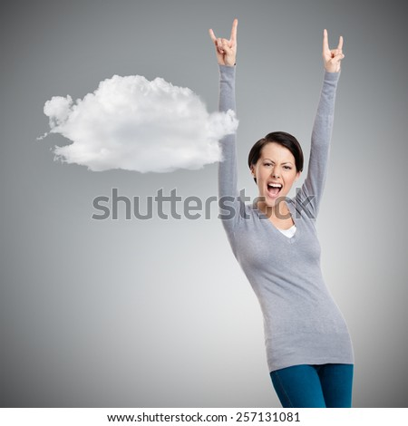 Glad pretty woman puts her hands up, grey background with cloud - stock photo