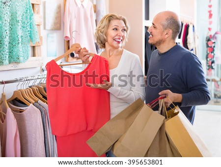 Glad senior husband helping charming wife to select dress at apparel store - stock photo