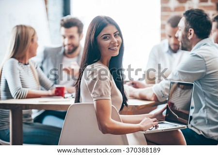 Glad to be a successful businesswoman. Cheerful young woman holding laptop on her knees and looking at camera while her colleagues discussing something in the background  - stock photo