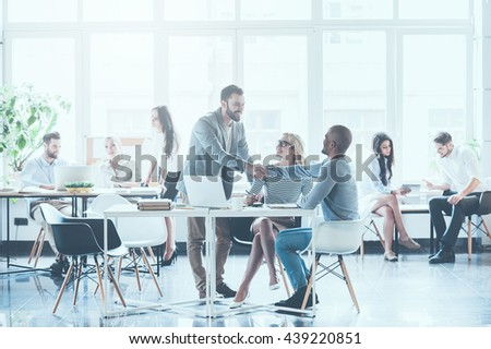 Glad to see you in team! Group of young business people working and communicating with each other in office while two men shaking hands and smiling - stock photo