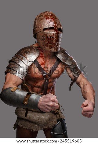 Gladiator in helmet with muscular body shows his strength - stock photo