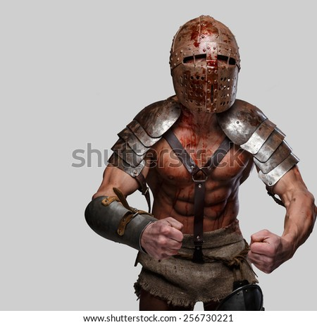 Gladiator in helmet with muscular body shows his strength. Isolated on grey. - stock photo