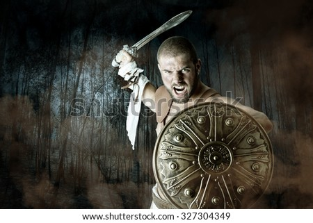 Gladiator or warrior posing with shield and sword battling in a dark forest