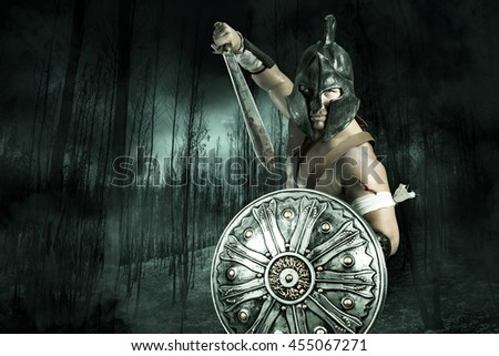 Gladiator or warrior posing with shield and sword outdoors ready for battle - stock photo