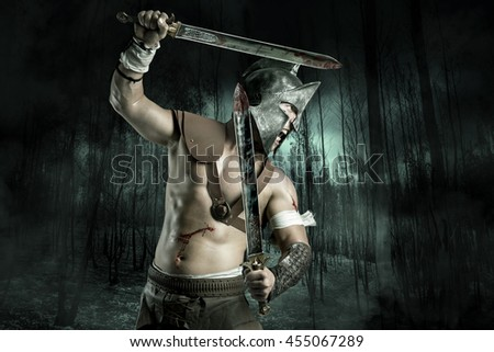 Gladiator or warrior posing with swords outdoors ready for battle