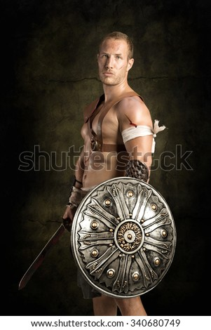 Gladiator posing isolated in a dark background - stock photo