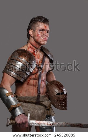 Gladiator with muscular body covered in blood with sword and helmet - stock photo