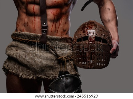 Gladiator with muscular body holding a helmet - stock photo