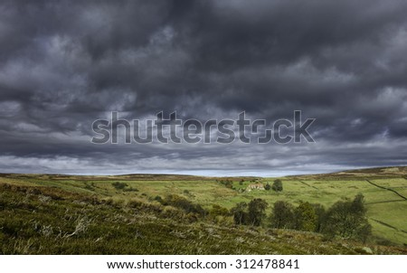 Glaisdale, Yorkshire, UK. Isolated farmhouse in the North York Moors under a stormy sky with sunlight breaking through on an autumn day near Glaisdale, Yorkshire, UK.