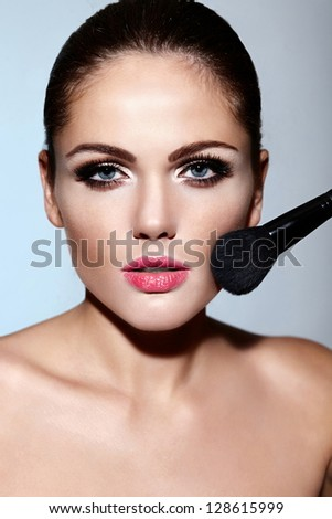 glamor closeup portrait of beautiful sexy Caucasian brunette young woman model with perfect clean skin applying makeup on her face - stock photo