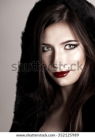 glamor closeup portrait of beautiful young woman model with bright professional makeup with perfect clean with red lips in fur coat. fashion - stock photo