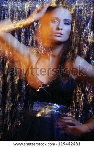 Glamor girl with bright makeup in black evening dress and beautiful jewelry dancing in motion  sparkle  lights - stock photo