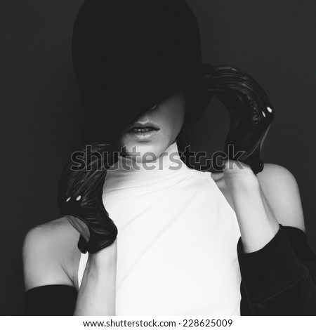 Glamor Model on black background in trendy gloves and hat autumn fashion style - stock photo