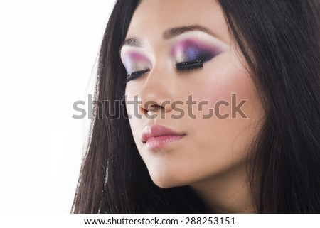 Glamor portrait of a beautiful brunette with colored eyes and light lipstick