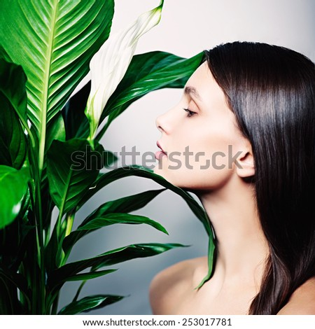 Glamor portrait of beautiful girl with green flower on a white background - stock photo