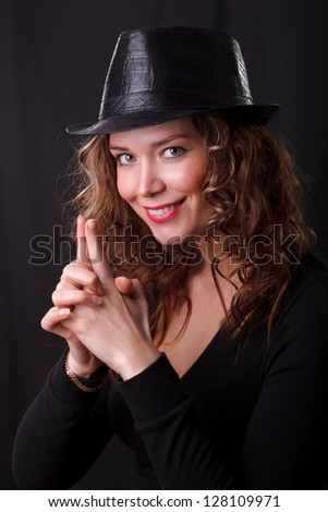 Glamor portrait of beauty woman smiling in dark hat make a joke pistol with her fingers