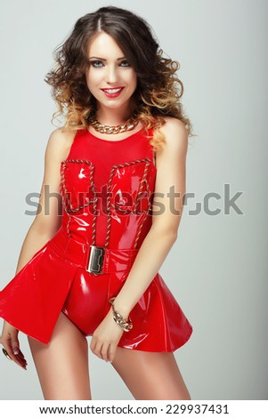 Glamor. Smiling Sensual Woman in Red Shiny Clothes - stock photo