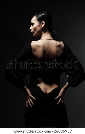 glamor woman in dress with naked back over black background