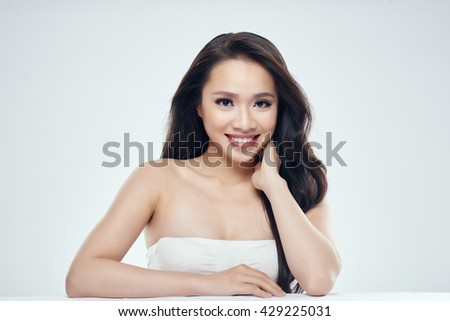 Glamorous Asian woman smiling at looking at camera - stock photo