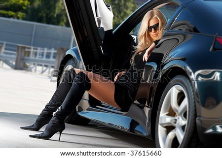 Glamorous blond babe sitting in tuned supercar - stock photo
