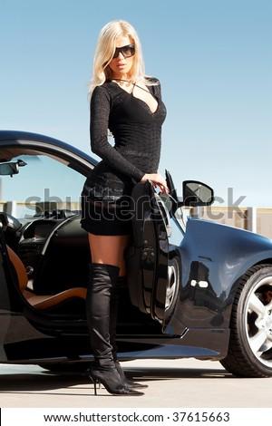 Glamorous blond babe standing near tuned supercar - stock photo