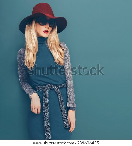 Glamorous Blond model in vintage Hat and Dress on green background - stock photo