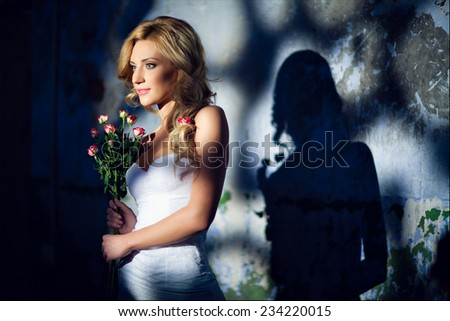 Glamorous blonde girl in a white dress with roses on the background wall - stock photo