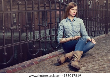Glamorous blonde woman in jeans and boots, sitting outside - stock photo