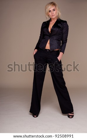 Glamorous blonde woman standing in a black slacksuit showing cleavage and belly button , studio on white - stock photo