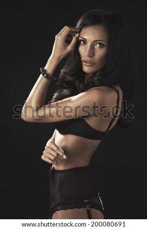 Glamorous busty brunette model with lovely long curly hair and a gorgeous figure posing in a black bikini on a  studio background   - stock photo