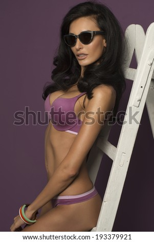 Glamorous busty brunette model with lovely long curly hair and a gorgeous figure posing in a violet bikini on a hot purple studio background with ladder  - stock photo