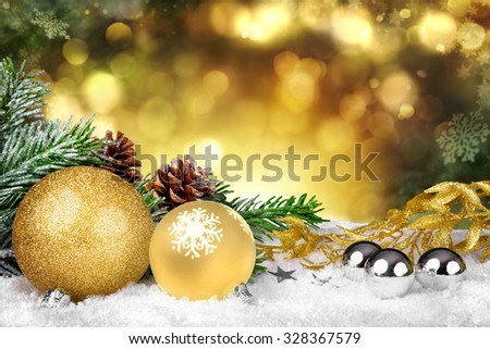 Glamorous Christmas scene with gold ornaments, fir branches and pine cones on snow and defocused shiny golden lights in the background - stock photo
