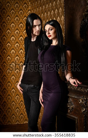 Glamorous couple in elegant evening dresses in vintage interior. Fashion shot.