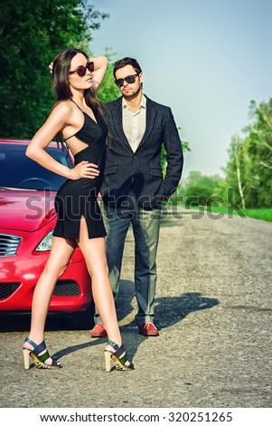 Glamorous couple near the car. Beauty, fashion. Love concept. - stock photo