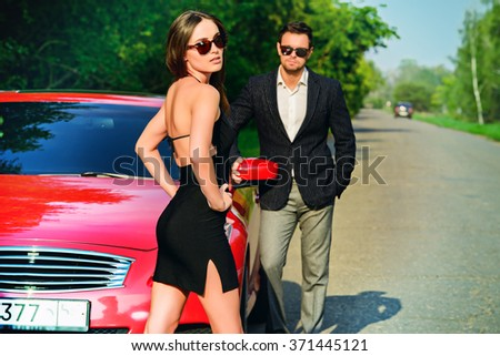 Glamorous couple near the car. Beauty, fashion. Love concept. - stock photo