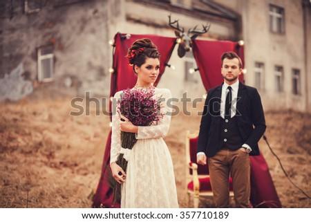 glamorous couple standing near the decor. focus on woman - stock photo