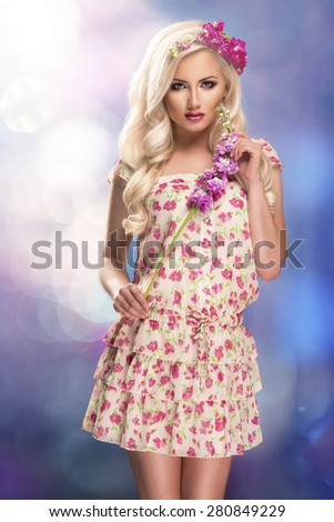 Glamorous curvy blonde woman with a sexy body posing with flowers - stock photo