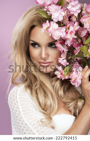 Glamorous curvy blonde woman with a sexy body posing with flowers on a pink studio background.  - stock photo